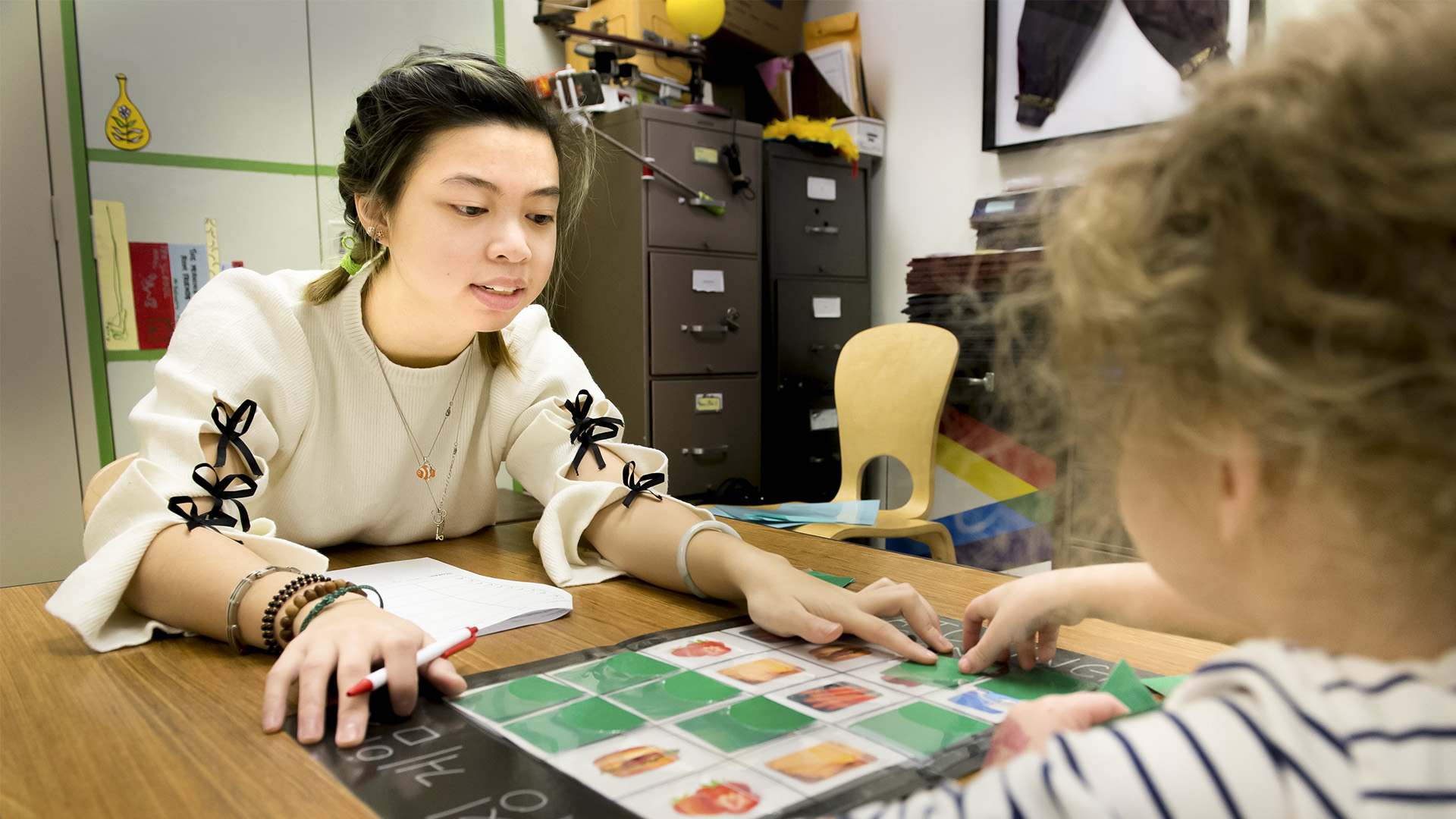 Dietrich College student plays a learning game with a child in the Children's School