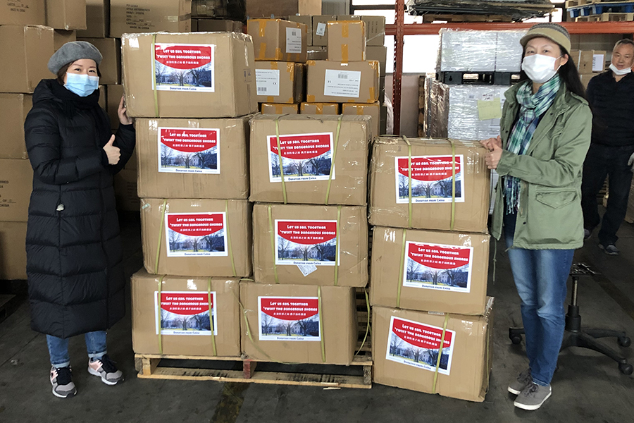 Two CMU parents in China stand with pallets of PPE supplies