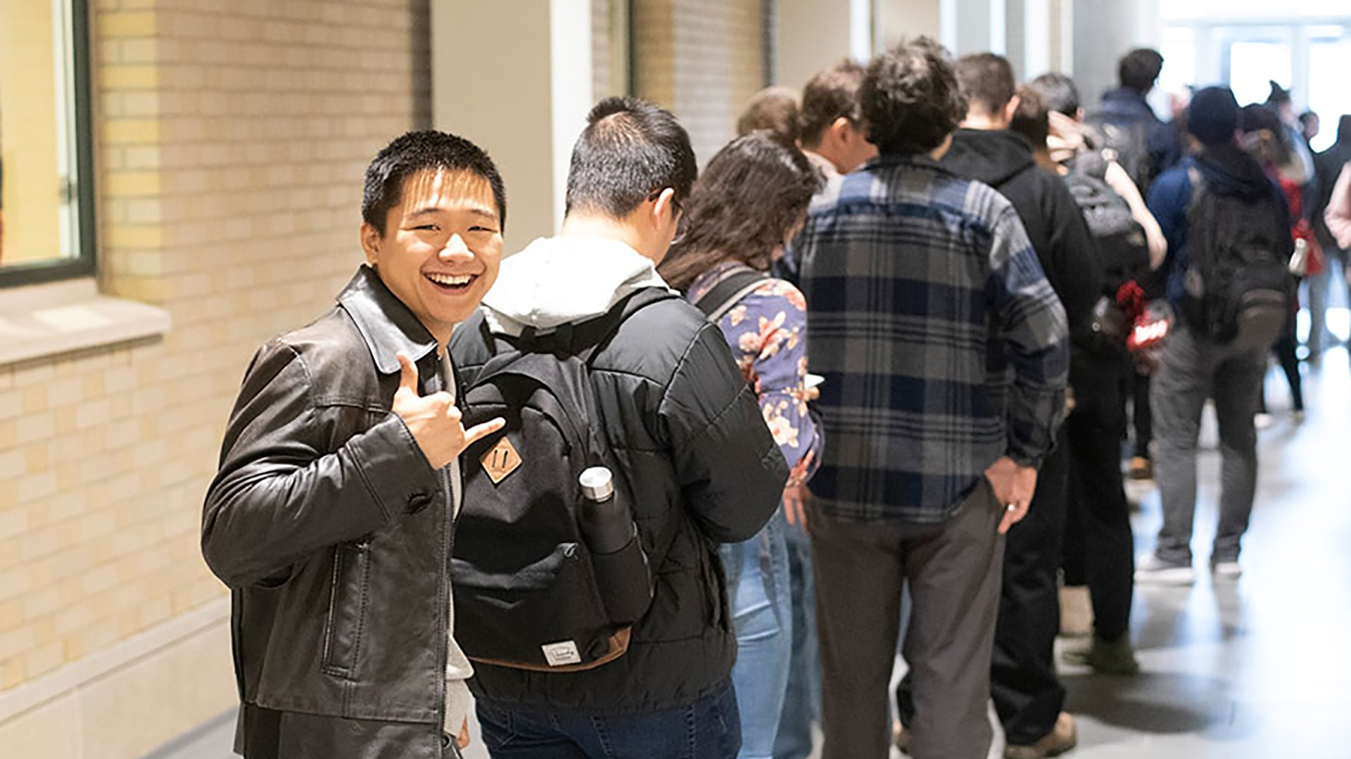Smiling student in line with other students