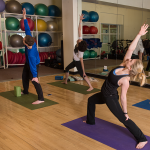 three people hold a yoga pose in a wellness room