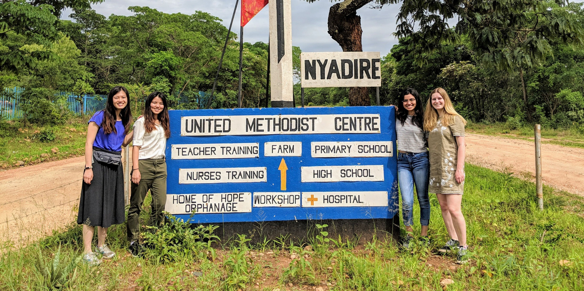 Group of students in front of a sign in Nyadire Zimbabwe
